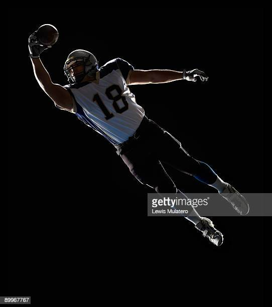 american football player leaping to catch ball - wide receiver athlete stock pictures, royalty-free photos & images