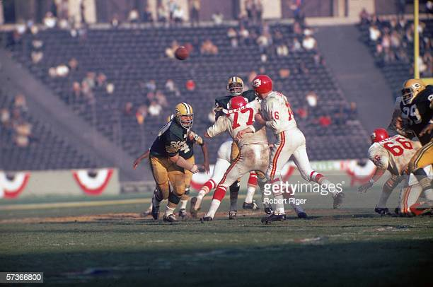 American football player Len Dawson , quarterback for the Kansas City Chiefs, throws the ball as opponant Lee Roy Coffey closes in during the first...