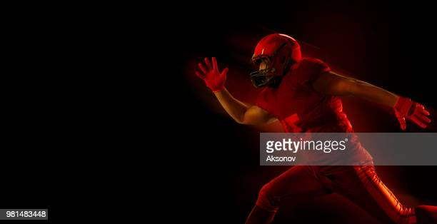 american football player on a dark red background - phosphorescence stock pictures, royalty-free photos & images