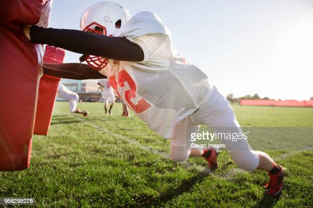 american football player pushing football sled on field - s'entraîner photos et images de collection