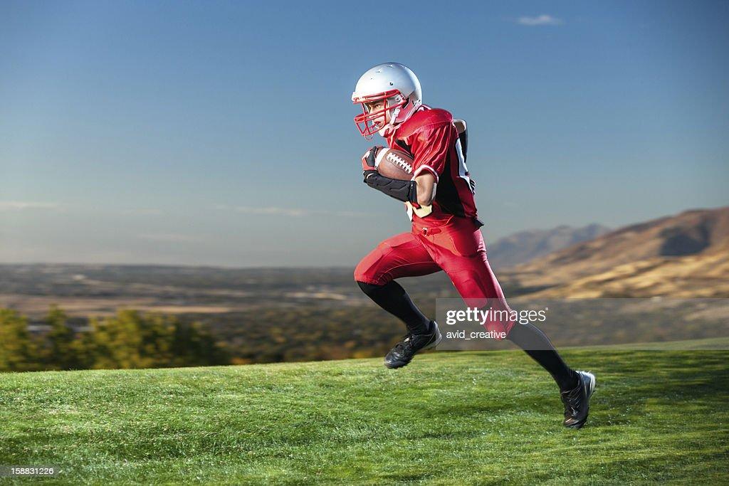 Jugador de fútbol americano en funcionamiento la pelota : Foto de stock