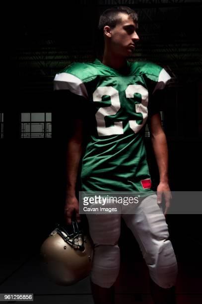 american football player standing while holding helmet - caneleira roupa desportiva de proteção imagens e fotografias de stock
