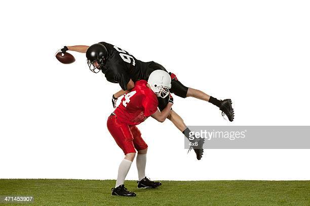 american football player tackling other man on the field - tackling stock pictures, royalty-free photos & images