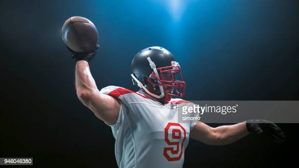 american football player throwing ball - safety american football player stock pictures, royalty-free photos & images
