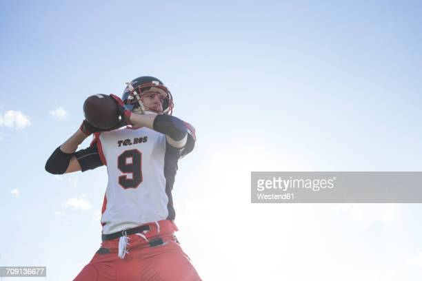 american football player throwing the ball during a match - quarterback stock photos and pictures
