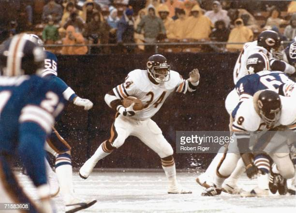 American football player Walter Payton of the Chicago Bears runs with the ball during a snowy game against the Nwe York Giants New York New York...