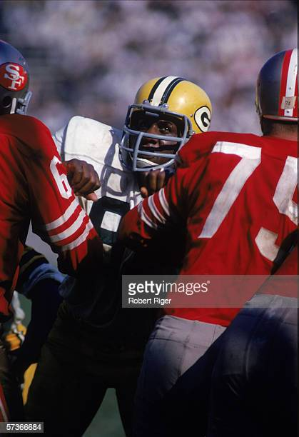 American football player Willie Davies of the Green Bay Packers attempts tp push his way between two opponants during a game against the San...