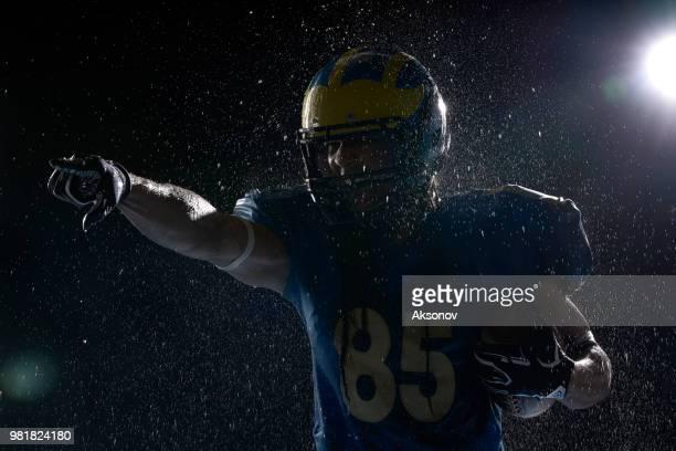 US-amerikanischer American-Football-Spieler mit Ball in einem Wasser sinkt auf schwarzem Hintergrund. Porträt