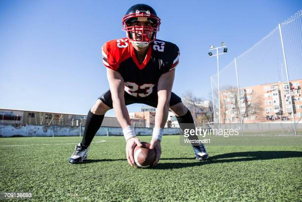 American football player with helmet and ball on sports field