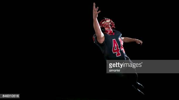 American football player  with one hand catching ball in the air on black background