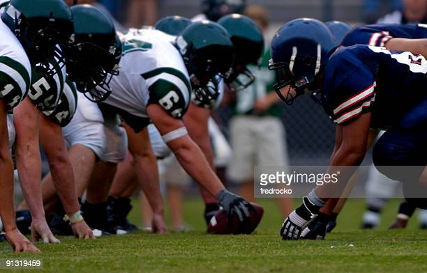 american football players at line of scrimmage during football game - football stockfoto's en -beelden