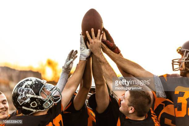 american football players celebrating the victory - squadra sportiva foto e immagini stock