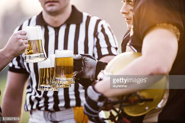 american football players celebrating victory with beer. - american football judge stock pictures, royalty-free photos & images