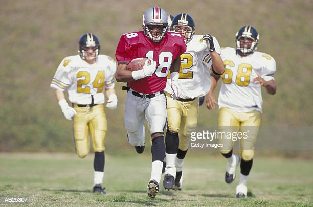 American Football players chasing ball carrier