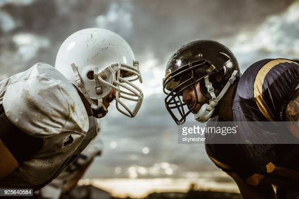 american football players confronting before the beginning of a match. - face off sports play stock photos and pictures