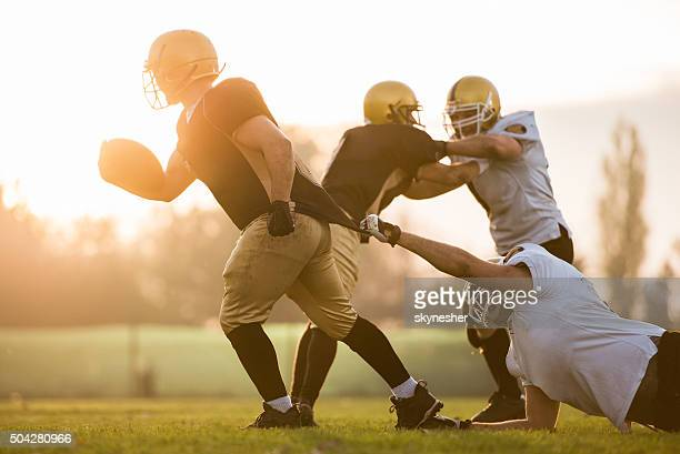 American football players during a match at sunset.