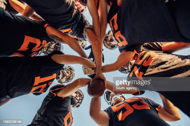 american football spelers huddling tijdens time-out - football stockfoto's en -beelden
