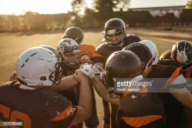 american football players huddling - huddling stock pictures, royalty-free photos & images