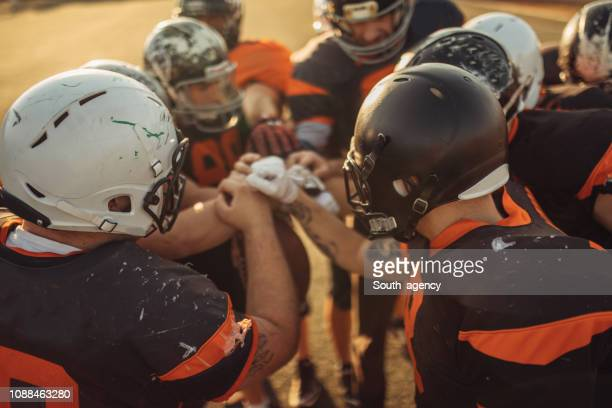 american football spelers huddling - football stockfoto's en -beelden