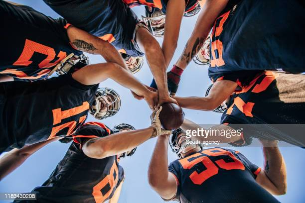 american football players huddling - american football team stock pictures, royalty-free photos & images
