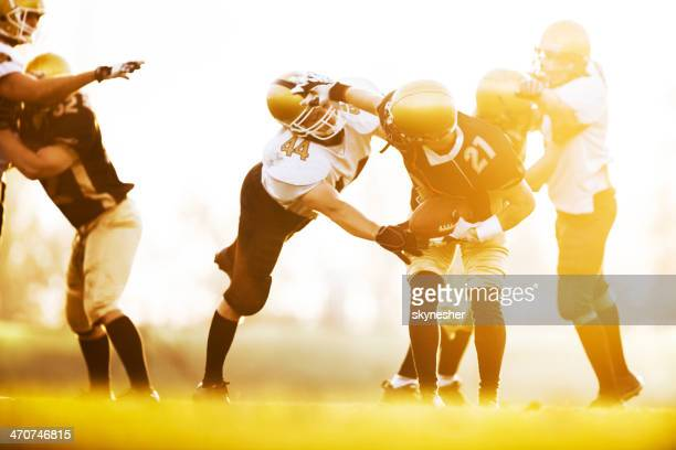 American football players in action at sunset.