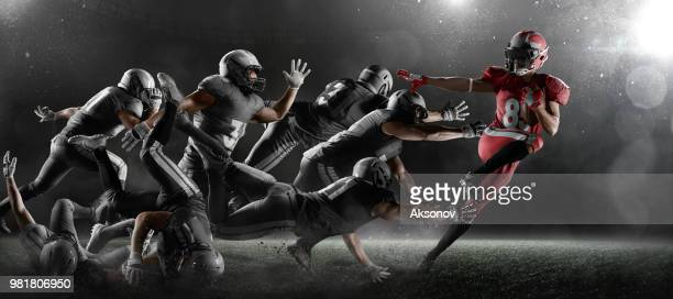 american football players in dark sport stadium - football player stock pictures, royalty-free photos & images
