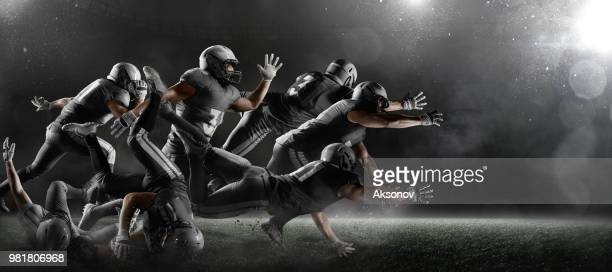 american football players in dark sport stadium - american football pitch stock pictures, royalty-free photos & images