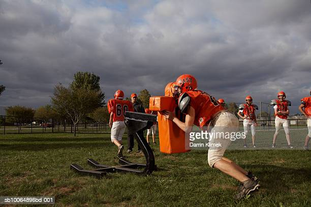 American football players including teenagers (15-17) training in field