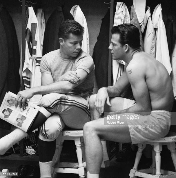American football players Kyle Rote and Frank Gifford of the New York Giants sit on stools as they chat in the locker room prior to the start of the...