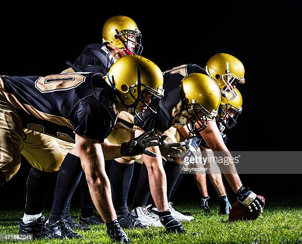 american football players lining up. - quarterback stock photos and pictures