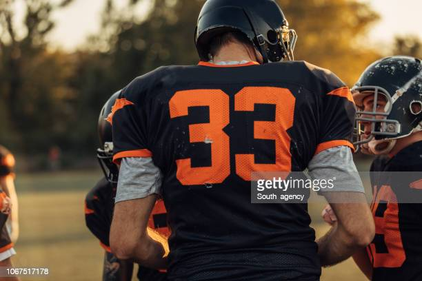 american football players on field - sports jersey stock pictures, royalty-free photos & images