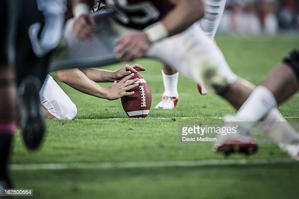 american football players readying to kick ball. - football stockfoto's en -beelden