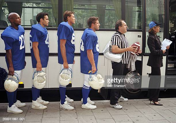 American football players, referee and coach in queue by bus, profile