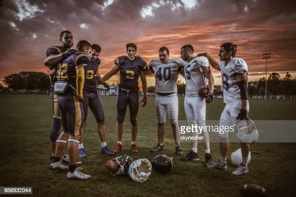 US-amerikanischer American-Football-Spieler stehen umarmte nach dem Spiel bei Sonnenuntergang.
