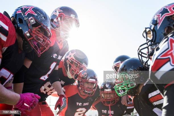 american football players talking and cheering in a circle before a game - huddling stock pictures, royalty-free photos & images