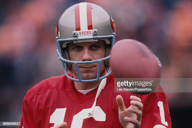 American football quarterback Joe Montana pictured with the ball playing for the San Francisco 49ers during Super Bowl XIX at Stanford Stadium in...