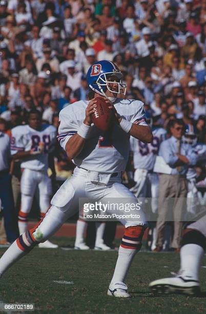 American football quarterback John Elway, pictured in action playing for the Denver Broncos against the Los Angeles Raiders at the Los Angeles...