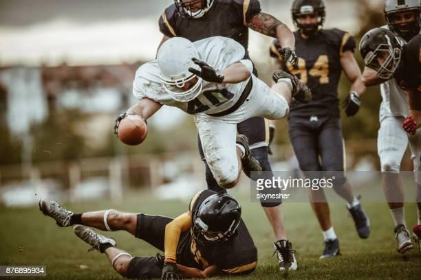 American football quarterback passing through defense for a touchdown.