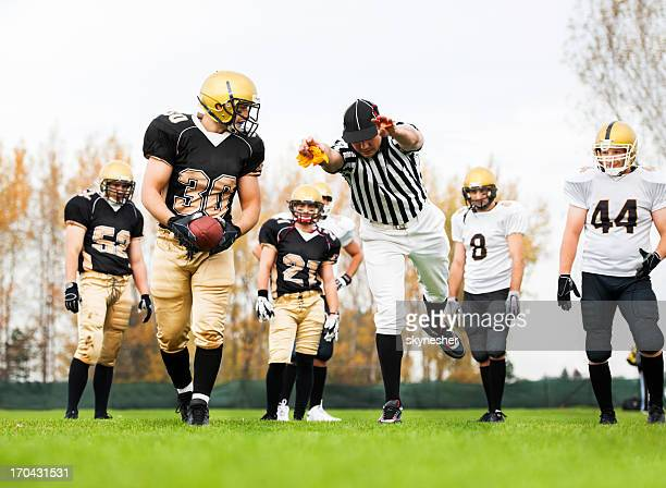American football referee showing the reason for foul.
