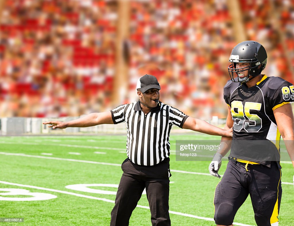 American football referee signals a play during the game. Player. : Stock Photo