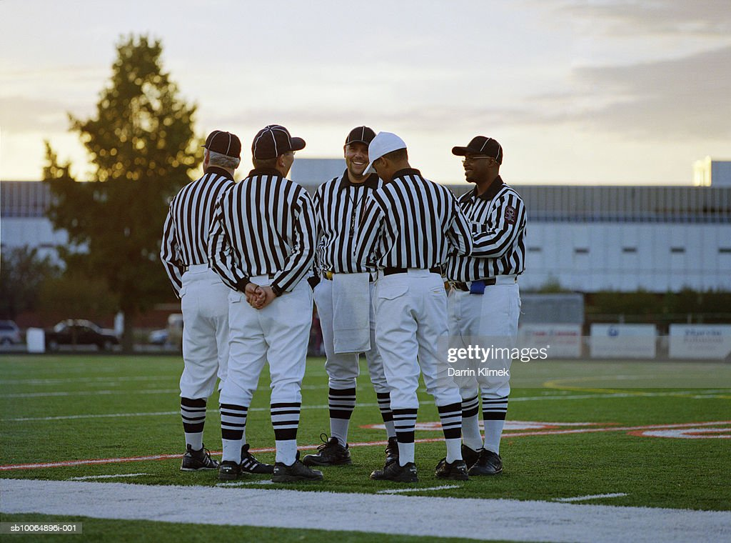 American football referees talking in field : Stock Photo