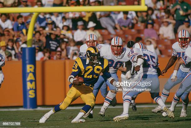 American football running back Eric Dickerson pictured in action with the ball playing for the Los Angeles Rams against the Houston Oilers at the...