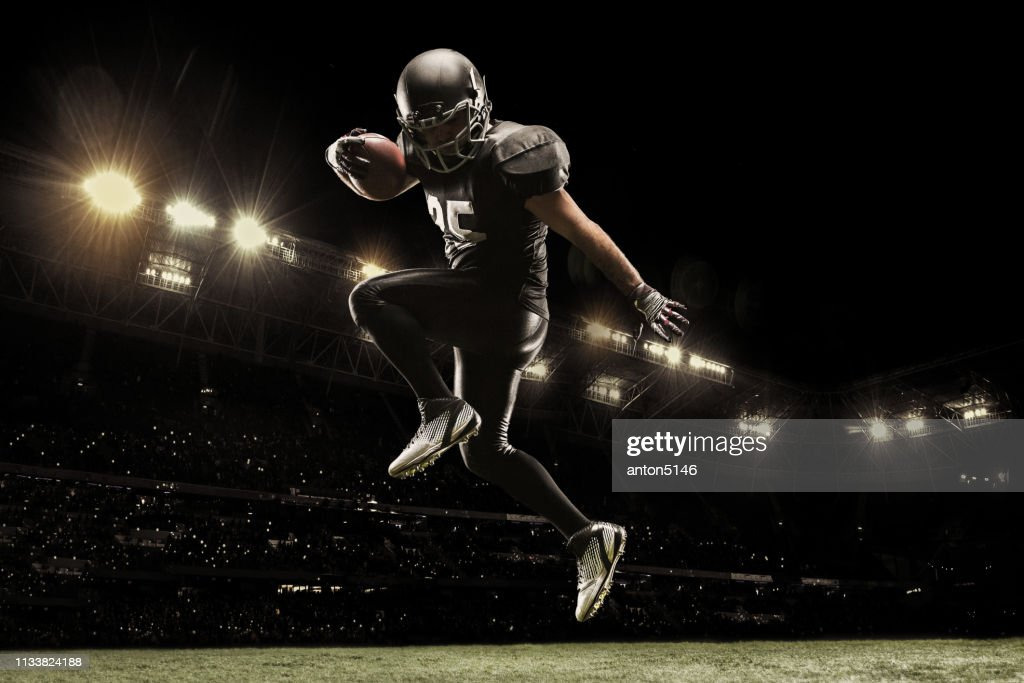 American football sportsman player on stadium running in action. Sport wallpaper with copyspace. : Foto stock