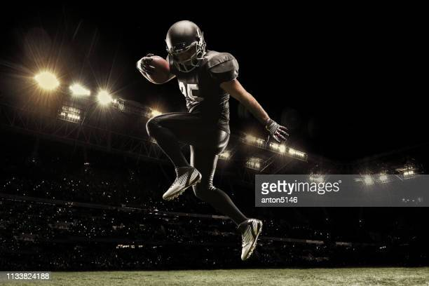 american football sportsman player on stadium running in action. sport wallpaper with copyspace. - quarterback stock pictures, royalty-free photos & images