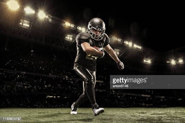 american football sportsman player on stadium running in action. sport wallpaper with copyspace. - touchdown stock pictures, royalty-free photos & images