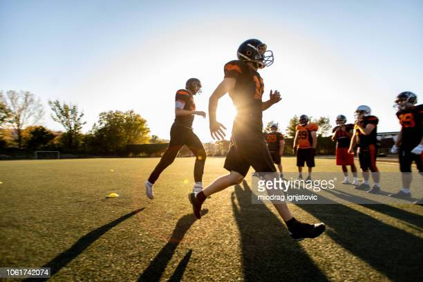 american football team in action - sports league stock pictures, royalty-free photos & images