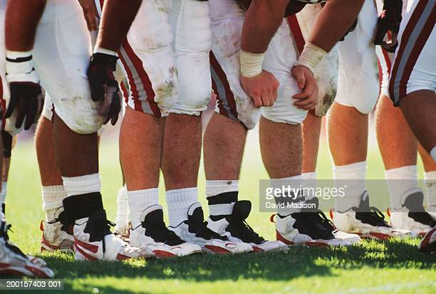american football team in huddle, low section (digital enhancement) - american football strip stock pictures, royalty-free photos & images