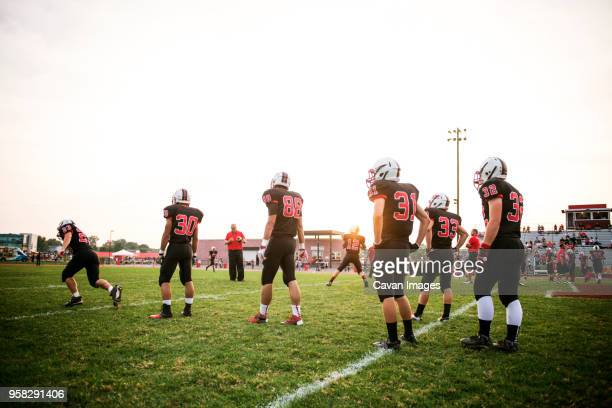 american football team playing on grassy field against sky - high school football stock pictures, royalty-free photos & images