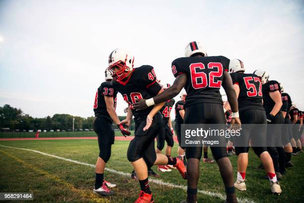 american football team practicing on grassy field against sky - high school football stock pictures, royalty-free photos & images