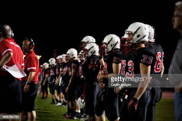 american football team standing in a row at field - high school football stock pictures, royalty-free photos & images